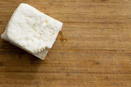 queso blanco: Cube of white cheese on cutting board with copy space for theme about specialty diary products ready to prepare Foto de archivo