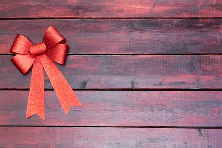 caoba: Elegante arco de Navidad rojo y cinta en la esquina superior de la caoba manchadas tablas de madera con espacio para copiar su tarjeta de saludo de temporada