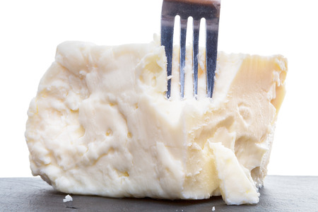 crumbly: Breaking semisoft crumbly full cream feta cheese made from cow milk with a fork showing the texture in a close up side view of the portion
