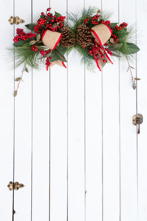 white door: White barn door with a festive red and burlap rustic Christmas decoration with berries and green foliage hanging at the top with copy space below for your holiday greeting Stock Photo
