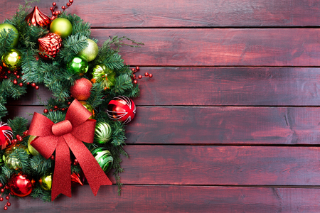 Elegant Christmas wreath with red and green baubles and a decorative fabric bow in a cropped view on mahogany stained wooden boards with copy space
