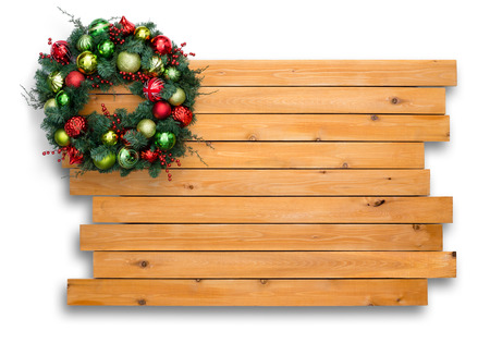 staggered: Colorful natural pine Christmas wreath arranged in the corner on a staggered cedar wood board background with copy space for your holiday greeting