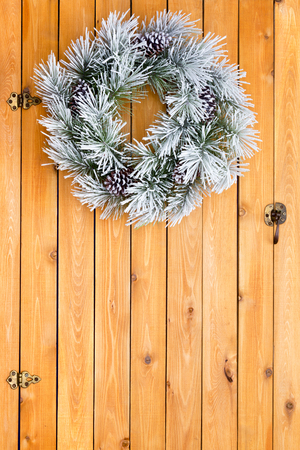 interspersed: Snowy white frosted Christmas wreath made from fresh evergreen pine foliage interspersed with cones hanging on a cedar wood barn door with copy space Stock Photo