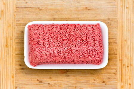 Close up on a container of fresh ground beef in retail packaging opened on a wooden cutting board ready to be prepared for a meal