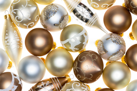Luxury Christmas ornament background on white with metallic gold, silver and copper colored decorations in a random pattern full frame view