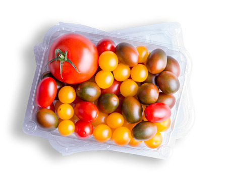 Top down view on various grape, medium sized and cherry tomatoes in clear plastic container over white background Stock Photo