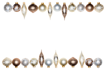 Double Christmas festive border of baubles and spindle shaped tree ornaments in wintry metallic tones isolated on white with central blank copy space