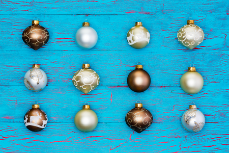 aligned: Neat array of metallic Christmas tree ornaments on an exotic tropical blue crackle paint background with the baubles arranged in aligned rows for a festive seasonal holiday background Stock Photo