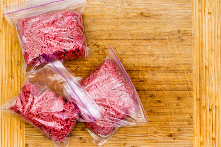 Fresh ground beef in resealable plastic bags ready to go into the freezer for storage on a wooden bamboo cutting board viewed from above with copy space
