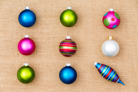 individualism: Festive Christmas still life with colorful Xmas tree ornaments arranged in neat rows of baubles with a single spindle conceptual of individualism and diversity