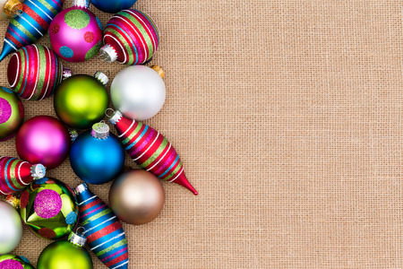 Colorful array of Christmas decorations on burlap with brightly colored baubles and spindles forming a side border with copy space for your holiday greeting Stock Photo