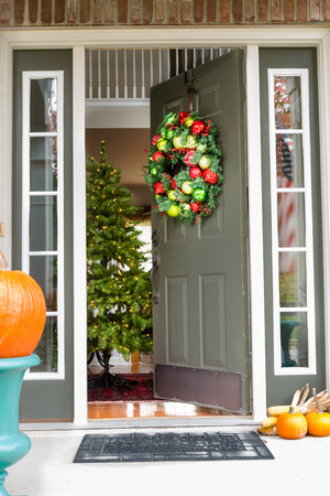 front of: Open doorway to an inviting Christmas scene with a colorful decorated wreath hanging on the wall and pumpkins on the porch in the foreground