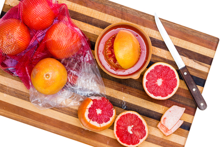 pectin: High Angle Still Life of Whole and Sliced Ruby Red Grapefruit Citrus on Wooden Cutting Board with Sharp Knife on White Background Stock Photo