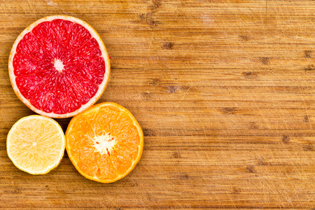 produces: High Angle Still Life View of Sliced Ruby Red Grapefruit, Orange and Lemon Arranged Together on Left Side of Frame on Rustic Wooden Cutting Board with Copy Space