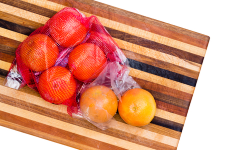 Bag of fresh healthy whole ruby grapefruit rich in vitamin c and soluble pectin fiber on a decorative striped cutting board