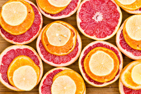 Full Frame, High Angle View of Sliced Ruby Red Grapefruit Stacked with Ripe Orange and Lemon Slices on Rustic Wooden Cutting Board
