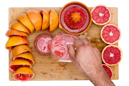 pectin: Man pouring freshly squeezed ruby grapefruit juice rich in soluble pectin fiber from a jug into a glass on a bamboo cutting board with a border of fresh cut halves and empty skins isolated on white Stock Photo