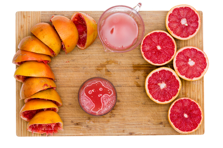 pectin: Preparing freshly squeezed ruby grapefruit juice with an overhead view of a bamboo board with empty rinds, juicy half fruit, a jug and glass of fresh juice rich in pectin soluble fiber