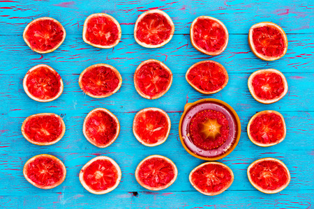 pectin: Freshly squeezed ruby grapefruit halves rich in pectin soluble fiber on an exotic blue crackle paint table with a manual juicer viewed from above in neat rows