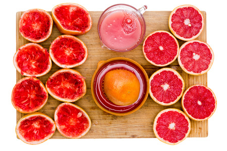 centered: Ruby grapefruit still life with juice and juicer centered on a bamboo cutting board wth freshly squeezed skins on one side and juicy halved fruit on the other, overhead view