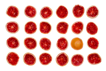 Rows of freshly squeezed ruby grapefruit halves viewed from above isolated on white with one rind placed upside down