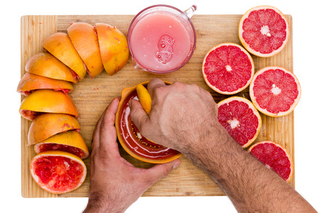 Hands of a man squeezing fresh ruby grapefruit halves on a manual juicer with fresh cut juicy fruit on one side and squeezed skins on the other on a bamboo cutting board Stock Photo