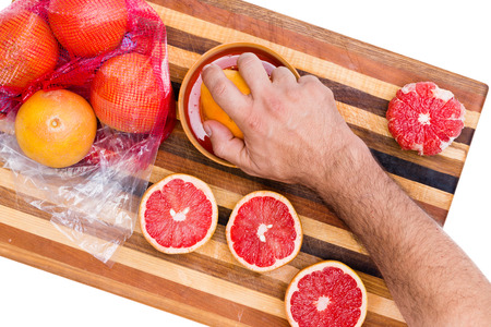 Man squeezing store bought fresh grapefruit on a manual juicer from a plastic packet of fresh fruit from the supermarket, overhead view on a stripe cutting board with juicy colorful pink cut halvess