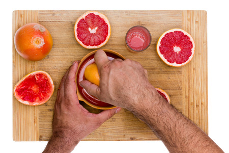 pectin: Man squeezing cut fresh ruby grapefruit halves on a manual juicer with a glass of fresh juice rich in pectin soluble fiber alongside, overhead view of the bamboo board and his hand isolated on white Stock Photo