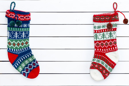 Two brightly colored empty woollen Christmas stocking waiting for Father Christmas arranged neatly to the side of a cedar wood plank background with copy space in the middle for your holiday greeting