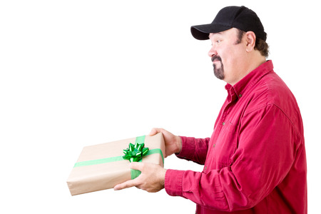 long sleeve shirt: Side view of cheerful bearded mature man in red long sleeve shirt giving, delivering or receiving a gift