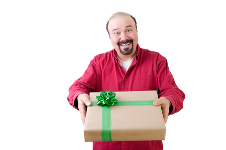 First person front view facing single smiling bearded mature man giving a gift wrapped in gold paper and green ribbon Stock Photo