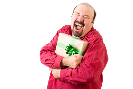screaming: Happy screaming man in red holding gift wrapped in gold paper and green ribbon over white background