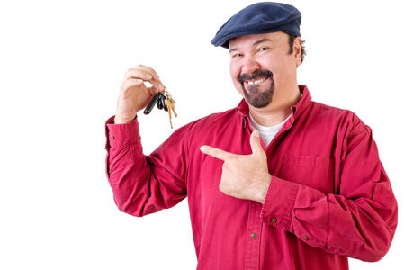 white achievement: Proud middle-aged man feeling very privileged in his achievement pointing to his new car keys with a satisfied happy smile, upper body on white