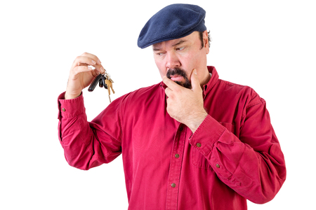 supposed: Confused man frowning at a bunch of car keys with a thoughtful expression as he ponders what he is supposed to do with them now that he has achieved his ambition of owning a car