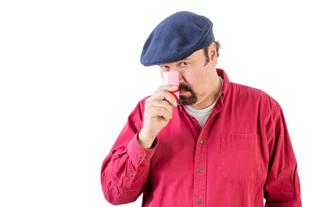 speculative: Suspicious middle-aged man wearing a cloth cap peering over his credit card with a speculative watchful expression as he holds it to his nose