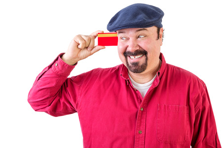 gleeful: Gleeful man eyeing his credit card with a beaming smile of anticipation as he imagines all the things he can go out and buy, upper body in a red shirt and cap isolated on white