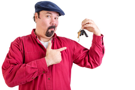 Jaunty proud big man in a cap standing pointing to his new set of car keys showing off and inviting attention and praise for his achievement, isolated on white Stock Photo