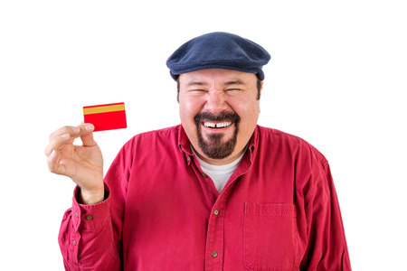 exuberant: Gleeful middle-aged man with a goatee wearing a red shirt and cap holding up a bank card with a beaming smile and laugh as he imagines all the items he can buy with it