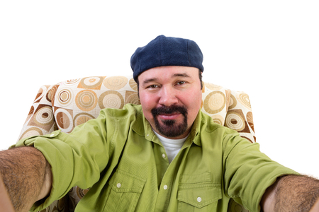 man with a goatee: Portrait of overweight man with goatee and beret in armchair taking selfie, white background Stock Photo