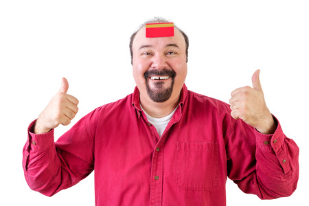 Happy man with thumbs up and credit card on forehead, white background