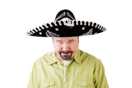 glowering: Grumpy middle aged man in Mexico sombrero hat looking downwards on white