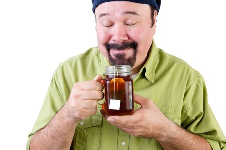 Middle aged man in beret smelling aromatic cup of herbal tea on white