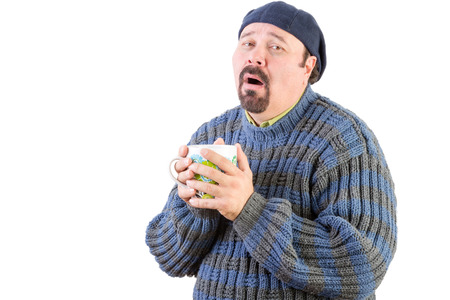 Poorly middle aged man in blue sweater with hot drink on white Stock Photo