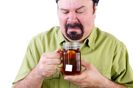 Uncertain middle aged man looking at herbal cup of tea on white