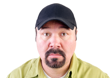 Portrait of staring man with goatee wearing baseball cap, white background