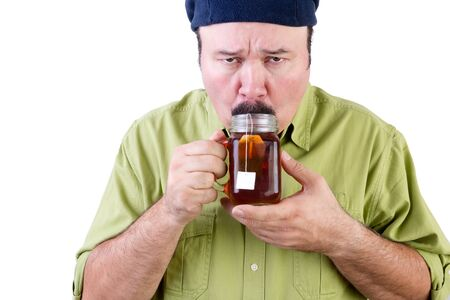 Portrait of unsure middle aged man in beret tasting cup of herbal tea on white