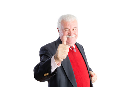 Senior in red sweater and business suit smiles and gives a thumbs up against a white background Stock Photo