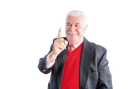 Cheeky senior wearing a business suit smiles at the camera and points upward