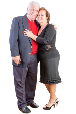 Loving elderly couple celebrating Valentines day standing in a close affectionate embrace smiling happily at the camera as they enjoy their lifelong commitment to each other Stock Photo