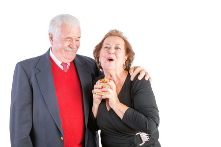 fond: Ecstatic senior woman receiving a Valentines gift from her loving husband reacting with joy as he watches with a fond smile, upper body isolated on white